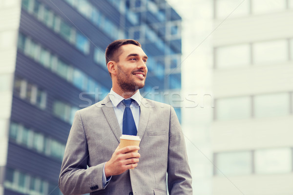 young smiling businessman with paper cup outdoors Stock photo © dolgachov