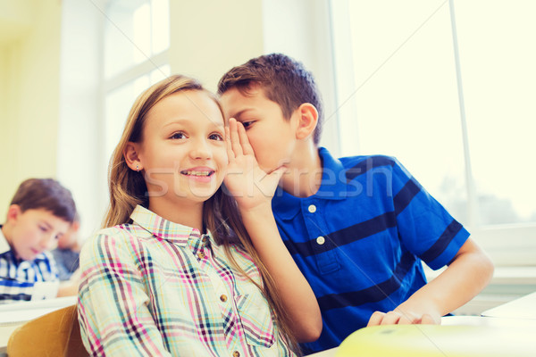smiling schoolboy whispering to classmate ear Stock photo © dolgachov