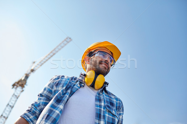 smiling builder with hardhat and headphones Stock photo © dolgachov