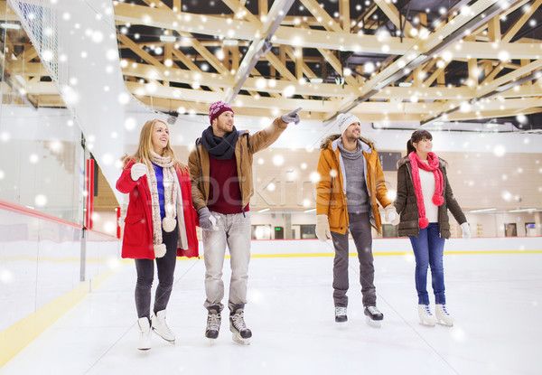 Stock photo: happy friends pointing finger on skating rink
