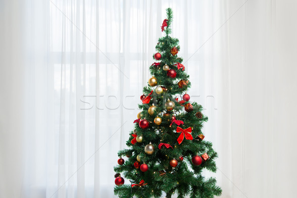 christmas tree in living room over window curtain Stock photo © dolgachov