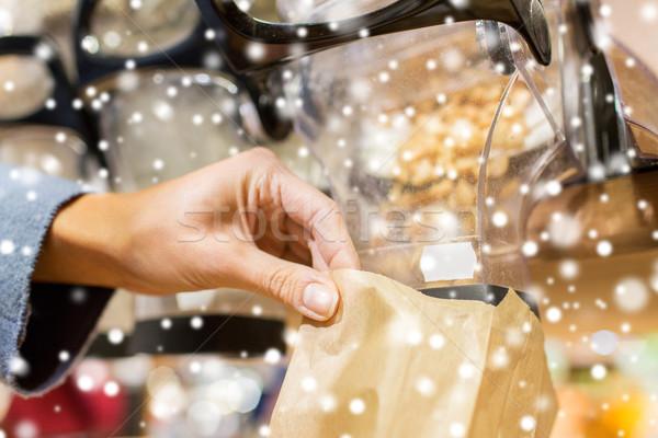 Közelkép kéz áramló diók papírzacskó vásár Stock fotó © dolgachov