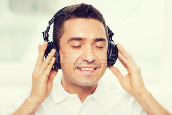 happy man in headphones listening to music at home Stock photo © dolgachov