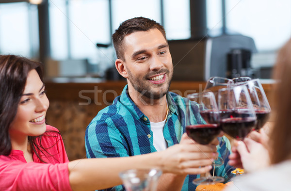 friends clinking glasses of wine at restaurant Stock photo © dolgachov