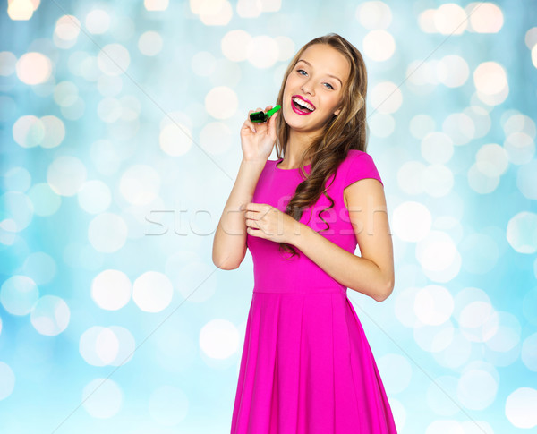Stock photo: happy young woman or teen girl with party horn