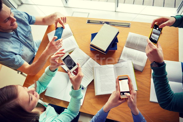 students with smartphones making cheat sheets Stock photo © dolgachov