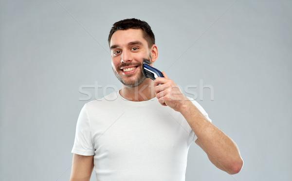 smiling man shaving beard with trimmer over gray Stock photo © dolgachov