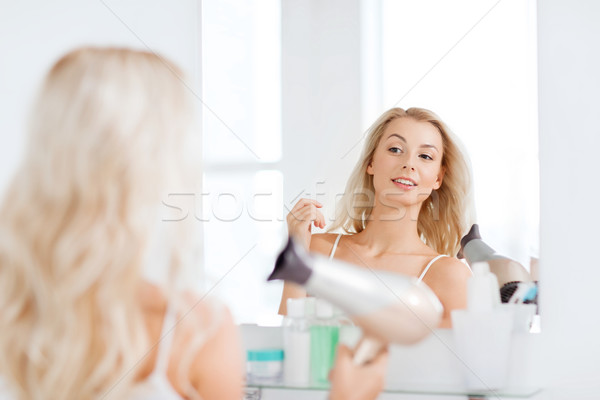 happy young woman with fan drying hair at bathroom Stock photo © dolgachov