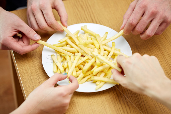 close up of hands taking french fries from plate Stock photo © dolgachov