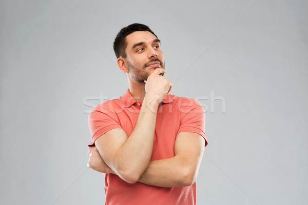 man in polo t-shirt thinking over gray background Stock photo © dolgachov