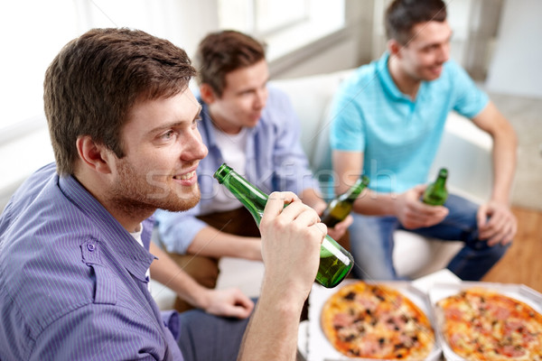 close up of friends with beer and pizza at home Stock photo © dolgachov