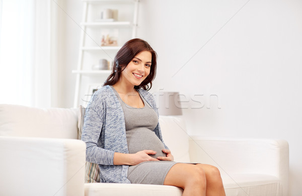 happy pregnant woman sitting on sofa at home Stock photo © dolgachov