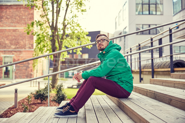 happy young hipster man sitting on stairs in city Stock photo © dolgachov