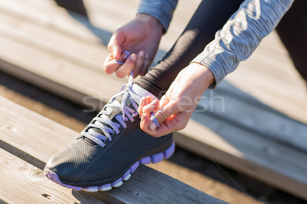 close up of sporty woman tying shoelaces outdoors Stock photo © dolgachov