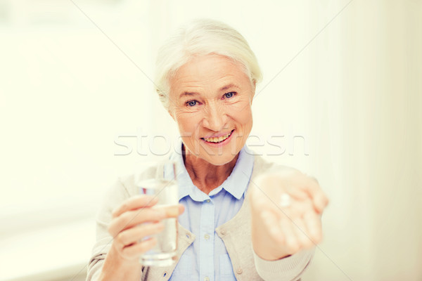 happy senior woman with water and medicine at home Stock photo © dolgachov
