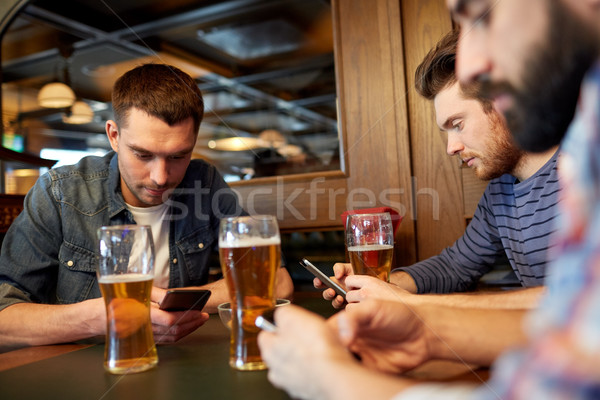 men with smartphones drinking beer at bar or pub Stock photo © dolgachov
