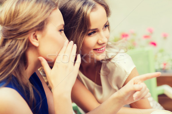 smiling young women gossiping at outdoor cafe Stock photo © dolgachov
