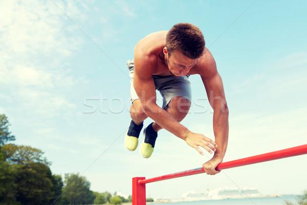 Młody człowiek poziomy bar odkryty fitness Zdjęcia stock © dolgachov