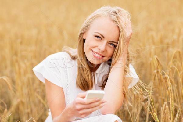 Szczęśliwy młoda kobieta smartphone zbóż dziedzinie lata Zdjęcia stock © dolgachov