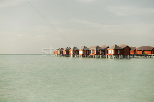 bungalow huts in sea water on exotic resort beach Stock photo © dolgachov
