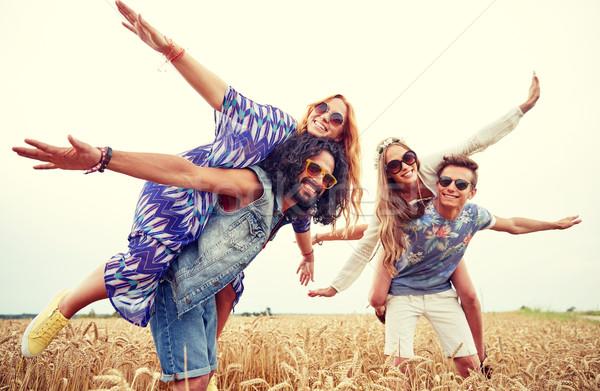 happy hippie friends having fun on cereal field Stock photo © dolgachov