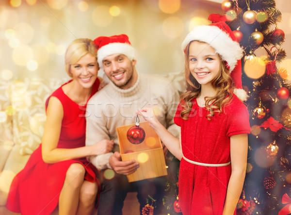 smiling family decorating christmas tree Stock photo © dolgachov