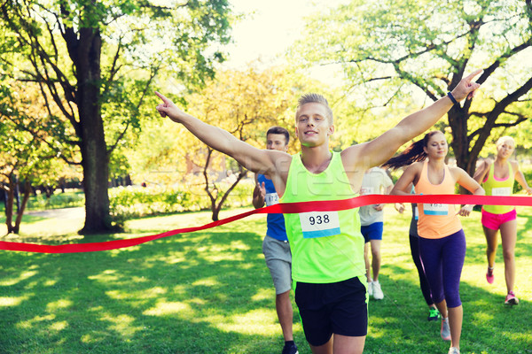 happy young male runner winning on race finish Stock photo © dolgachov