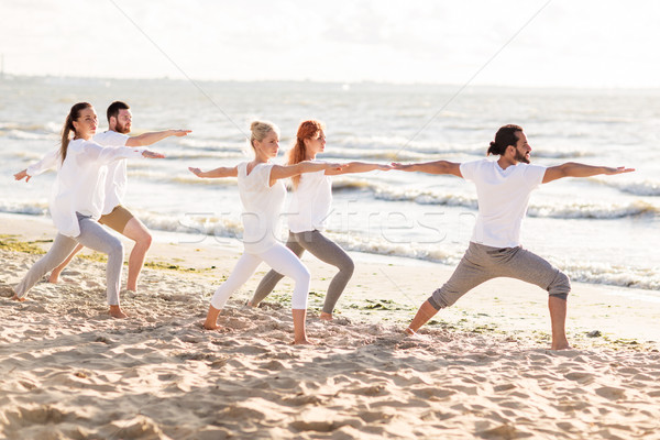 people making yoga in warrior pose on beach Stock photo © dolgachov