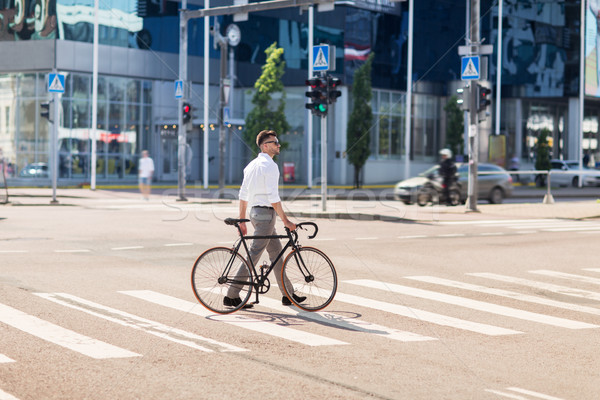 young man with bicycle on crosswalk in city Stock photo © dolgachov