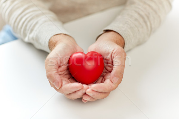 close up of senior man with red heart in hands Stock photo © dolgachov