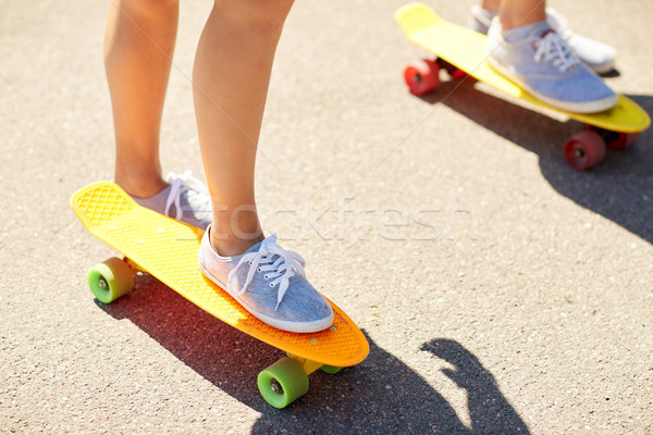 Stock photo: close up of female feet riding short skateboard