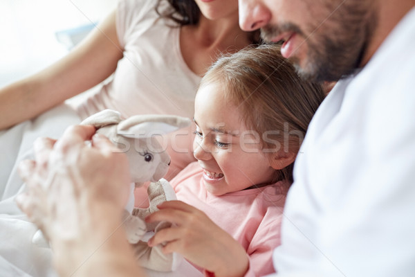 happy child with toy and parents in bed at home Stock photo © dolgachov