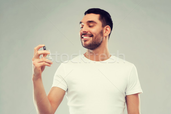 smiling man with male perfume over gray background Stock photo © dolgachov