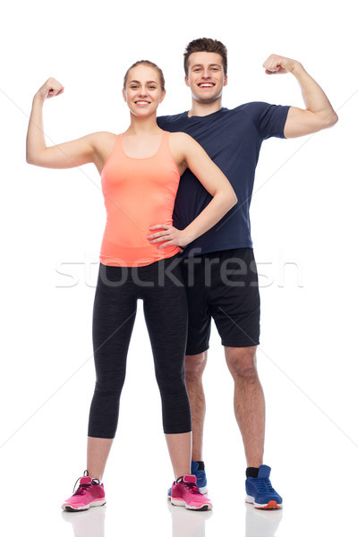 happy sportive man and woman showing biceps power Stock photo © dolgachov