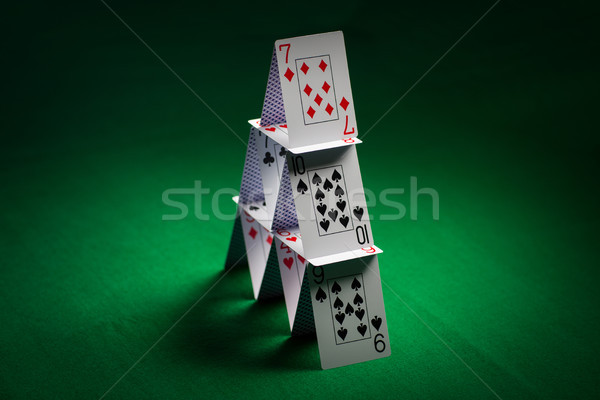 house of playing cards on green table cloth Stock photo © dolgachov