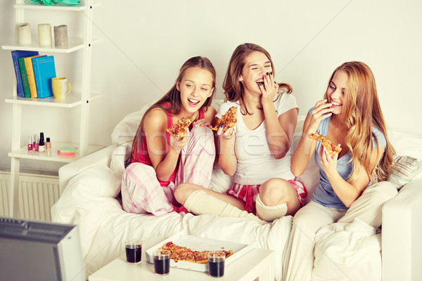 happy friends eating pizza and watching tv at home Stock photo © dolgachov