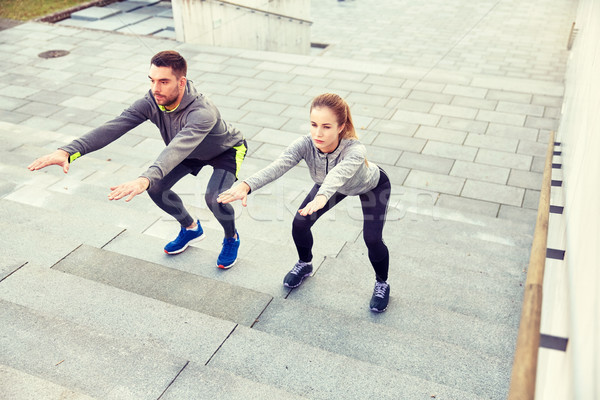couple doing squats on city street stairs Stock photo © dolgachov