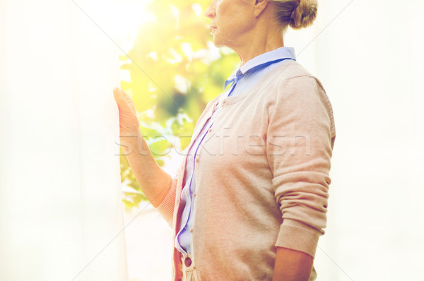 lonely senior woman looking through window at home Stock photo © dolgachov