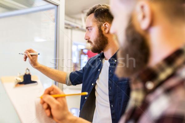 men writing to clipboard and whiteboard at office Stock photo © dolgachov