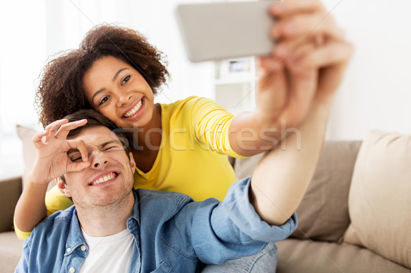 happy couple with smartphone taking selfie at home Stock photo © dolgachov