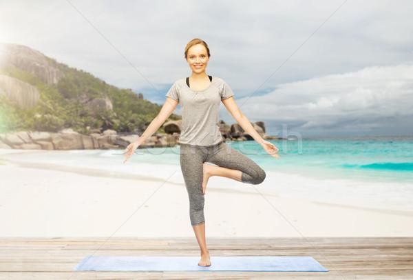 woman doing yoga in tree pose on beach Stock photo © dolgachov