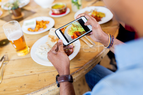 hands with smartphone picturing food at restaurant Stock photo © dolgachov