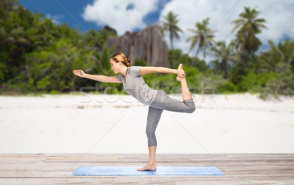 woman in yoga lord of the dance pose on beach Stock photo © dolgachov