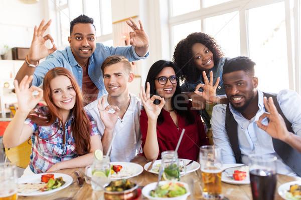 Heureux amis signe de la main restaurant Photo stock © dolgachov