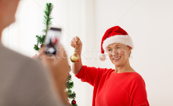 happy senior woman decorating christmas tree Stock photo © dolgachov