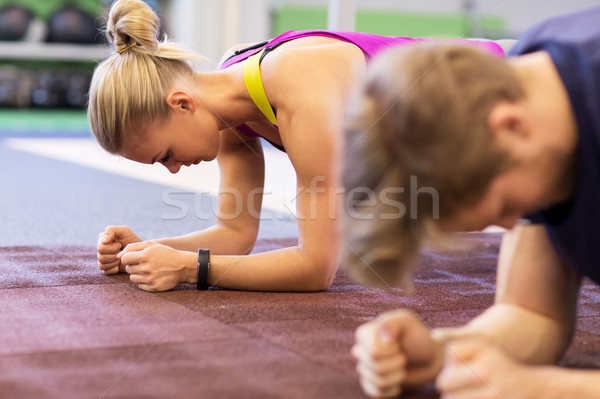 woman and man doing plank exercise in gym Stock photo © dolgachov