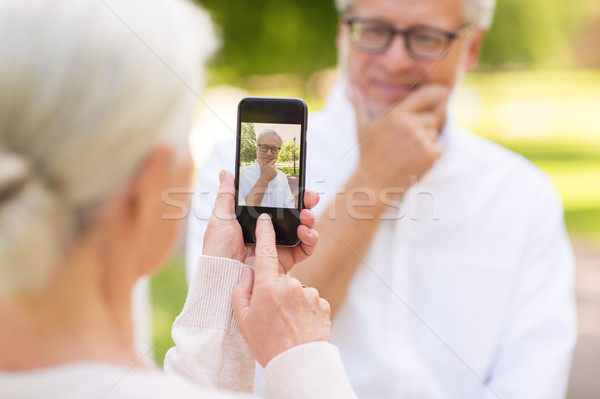 old woman photographing man by smartphone in park Stock photo © dolgachov