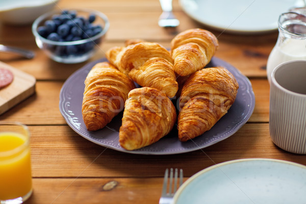 plate of croissants on wooden table at breakfast Stock photo © dolgachov