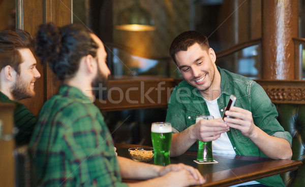 Vrienden smartphone drinken groene bier pub Stockfoto © dolgachov