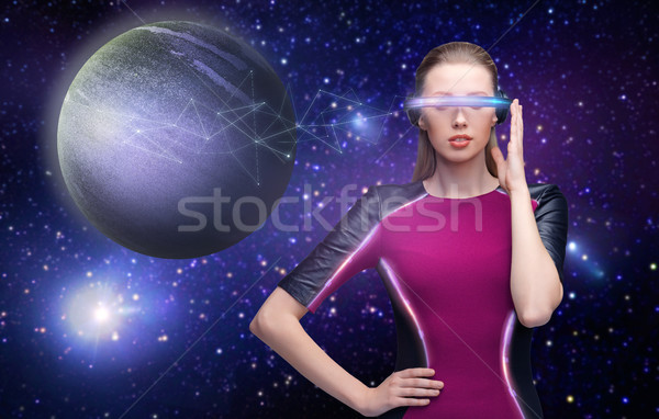 woman in virtual reality glasses over space Stock photo © dolgachov